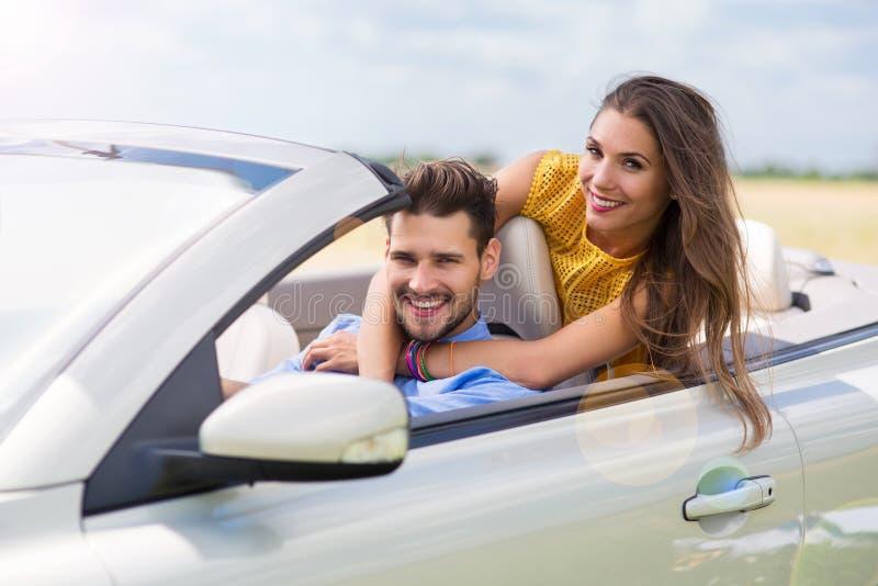 Equitação do homem novo e da mulher no carro convertível fotos de stock royalty free
