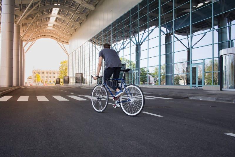 Equitação do homem novo na bicicleta na rua da cidade Homem na bicicleta azul com rodas brancas, fundo grande das janelas do espe imagens de stock