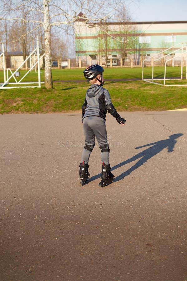 Equitação do menino em patins de rolo no parque imagens de stock royalty free