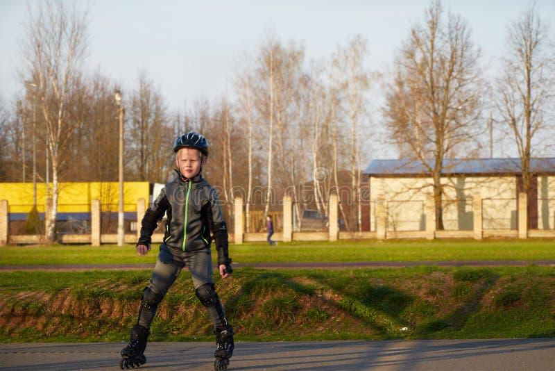 Equitação do menino em patins de rolo no parque fotografia de stock royalty free
