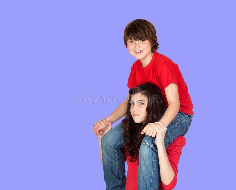 Equitação do menino em sua irmã imagem de stock royalty free