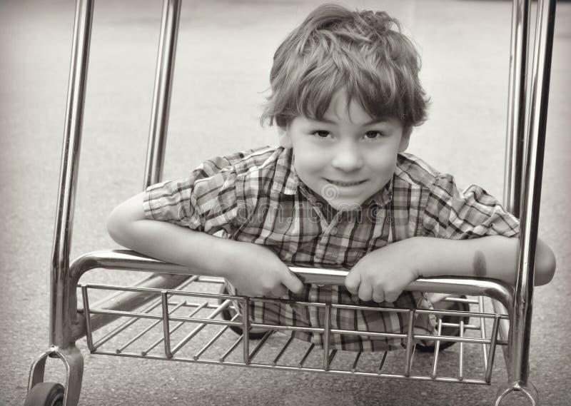Equitação do menino no carrinho de compras foto de stock
