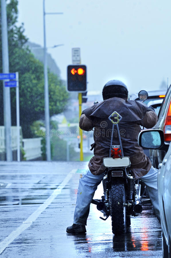 Equitação do motociclista da motocicleta na chuva no tráfego de cidade da manhã fotografia de stock