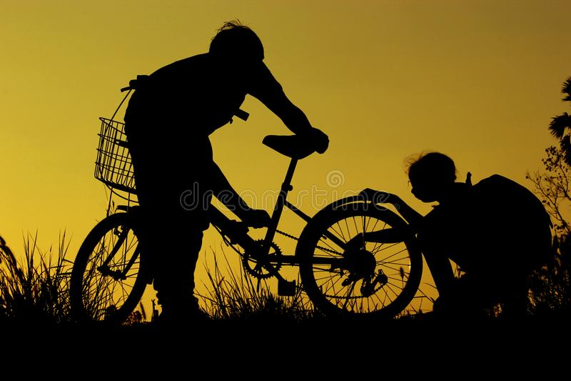 A equitação do rapaz pequeno e da menina bikes no por do sol, crianças ativas ostenta, criança asiática, mostra em silhueta uma c foto de stock royalty free