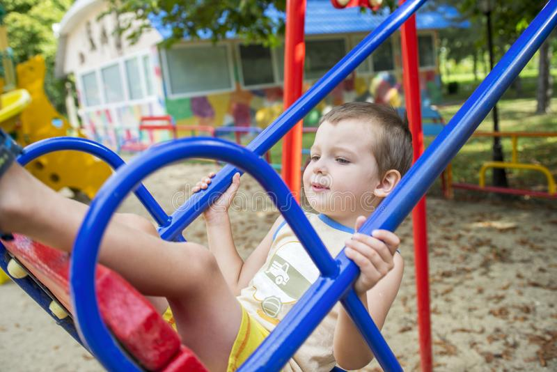 Equitação do rapaz pequeno em um balanço em um parque imagem de stock