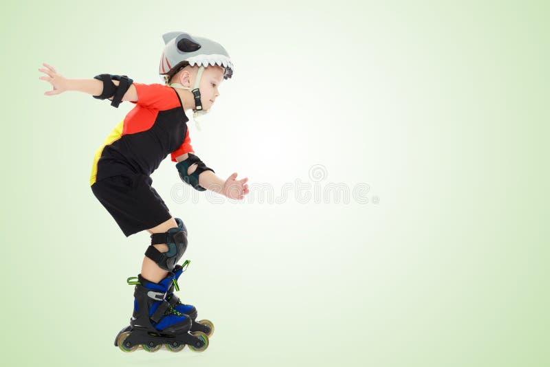 Equitação do rapaz pequeno nos rolos imagem de stock
