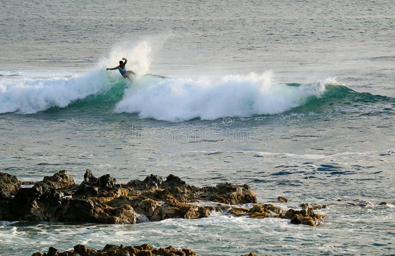 Equitação do surfista nas ondas de quebra no Oceano Pacífico em Hanga Roa, Ilha de Páscoa, o Chile imagens de stock