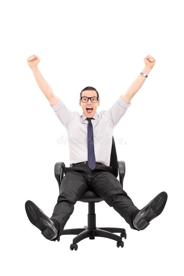 Equitação extático do homem em uma cadeira do escritório imagens de stock royalty free
