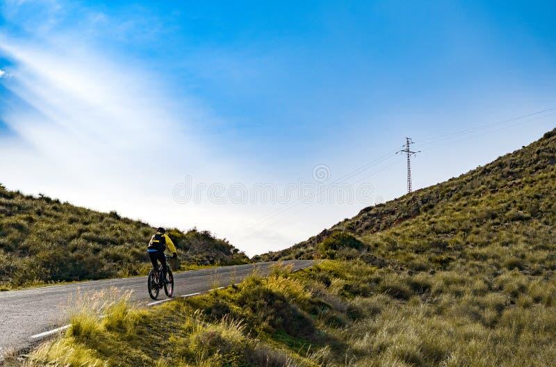 Equitação fêmea do ciclista do Mountain bike subida ao longo da estrada da montanha na Espanha imagem de stock royalty free