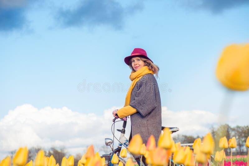 Equitação fêmea sua bicicleta através dos campos da tulipa foto de stock