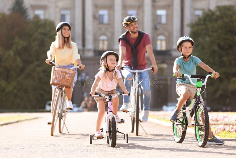 A equitação feliz da família bicycles fora fotografia de stock