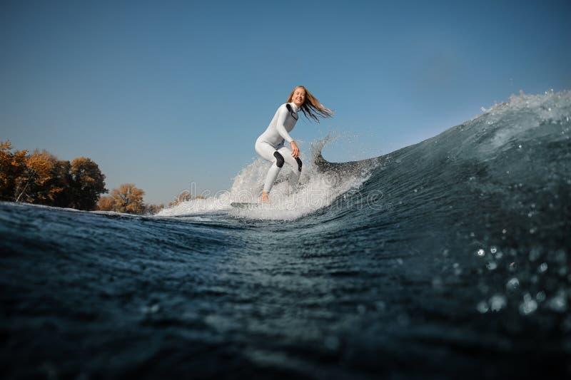 Equitação loura de sorriso da menina no wakeboard nos joelhos de dobra imagens de stock