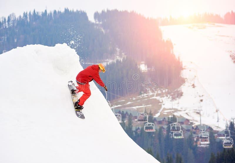 Equitação masculina do snowboarder da parte superior da inclinação nevado com o snowboard na estância de esqui do inverno fotos de stock royalty free