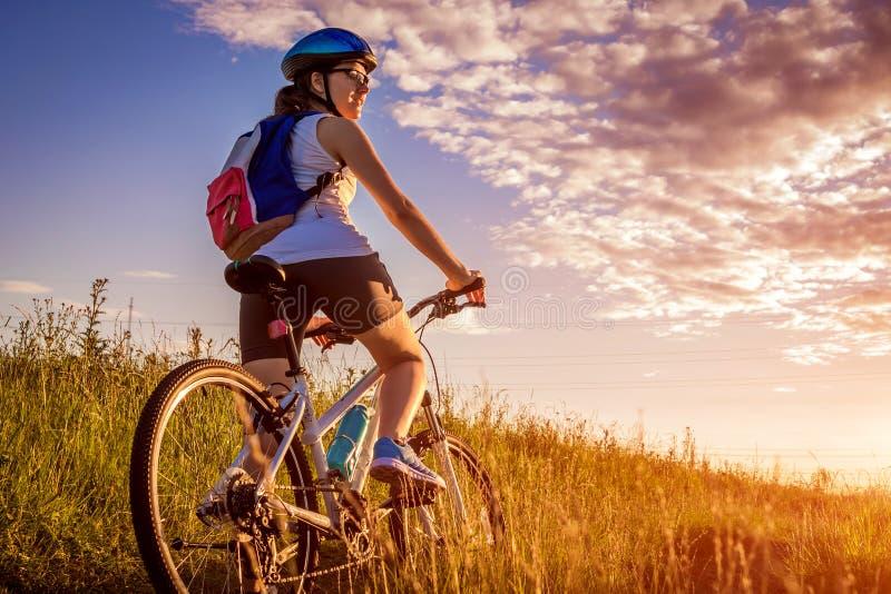 Equitação nova do ciclista no campo do verão Conceito saudável do estilo de vida fotos de stock royalty free