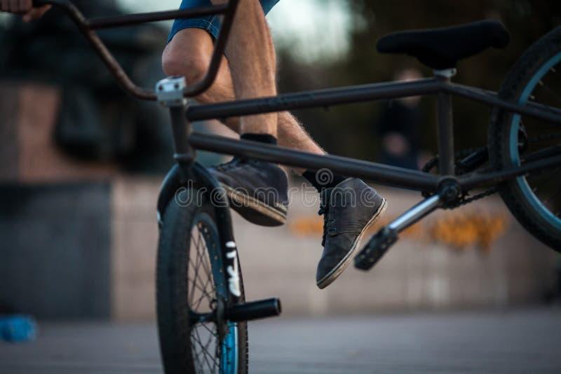Equitação nova do menino do ciclista do adolescente no backgro masculino do close up da parte mais inferior do passatempo do espo imagens de stock royalty free