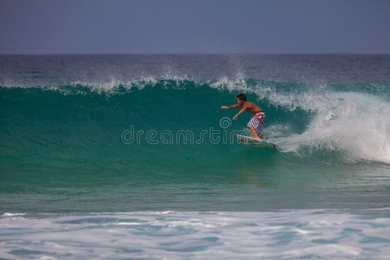 Equitação nova do surfista foto de stock