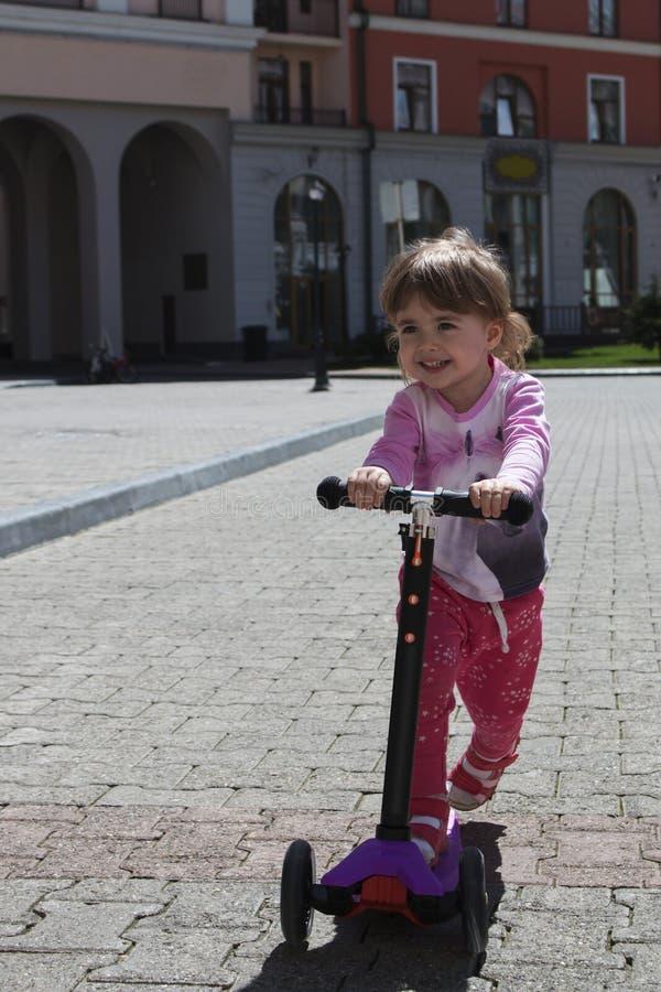 Equitação positiva de sorriso da menina no 'trotinette' na cidade fotografia de stock royalty free