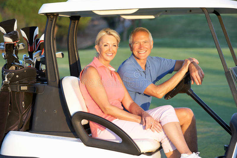 Equitação sênior dos pares no Buggy do golfe imagem de stock
