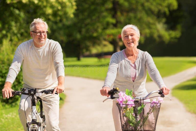 A equitação superior feliz dos pares bicycles no parque do verão imagem de stock royalty free