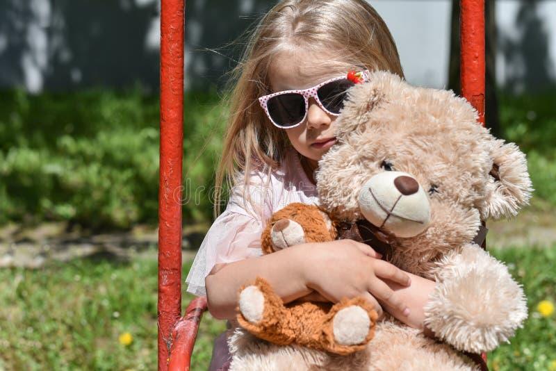 Equita??o triste da menina no balan?o velho com um urso de peluche imagens de stock royalty free
