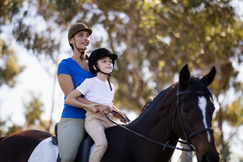 Equitación de enseñanza de la mujer a la muchacha imagen de archivo libre de regalías