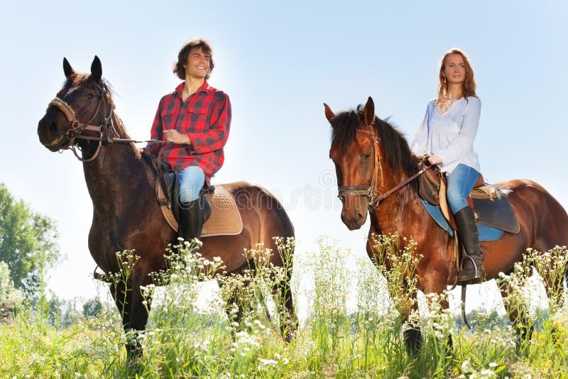 Equitación feliz de los pares en prados floridos foto de archivo libre de regalías
