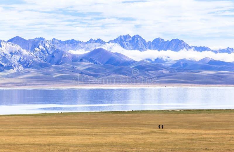 Equitazione nel lago del kul di canzone nel Kirghizistan fotografia stock libera da diritti
