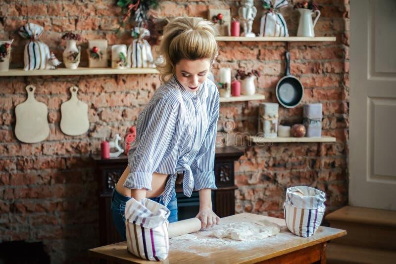 Erótico louro da jovem mulher 'sexy' prepara a massa na cozinha dona de casa com os sacos da farinha e com o pino do rolo na cozi foto de stock