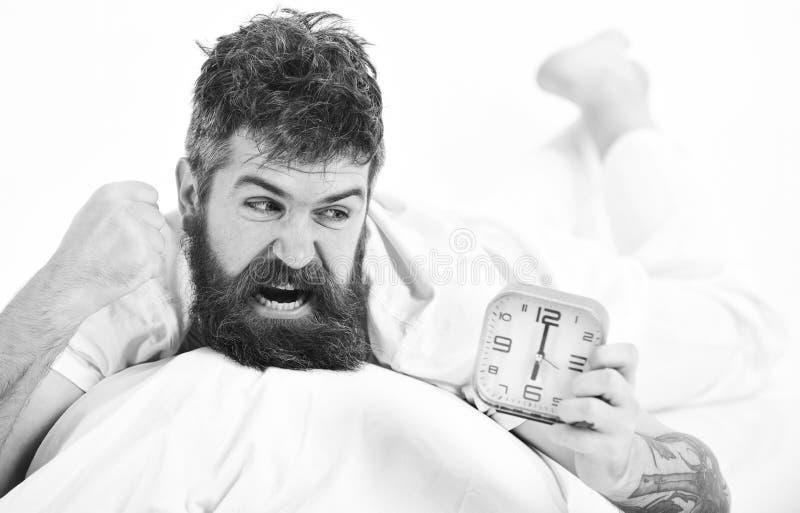 Er bedroht seine Hand am Wecker, Versuch, um zu zerstören Fühlen wütend Verärgerter Kerl im Bett morgens stockfoto