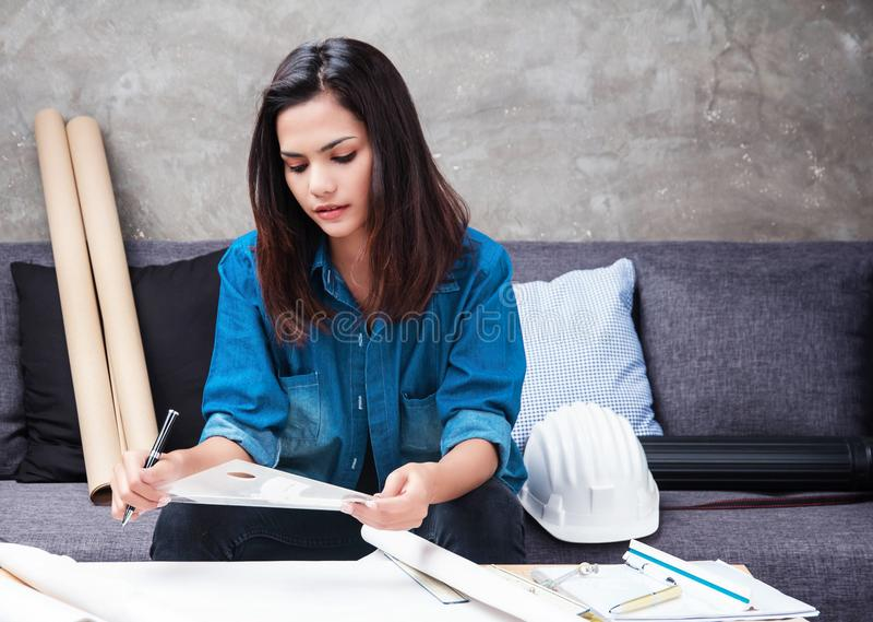 Er der junge weibliche Architekt, der an Projekt arbeitet, sie benutzt Architektenwerkzeug für Arbeit, Griffstift in der Hand lizenzfreies stockfoto