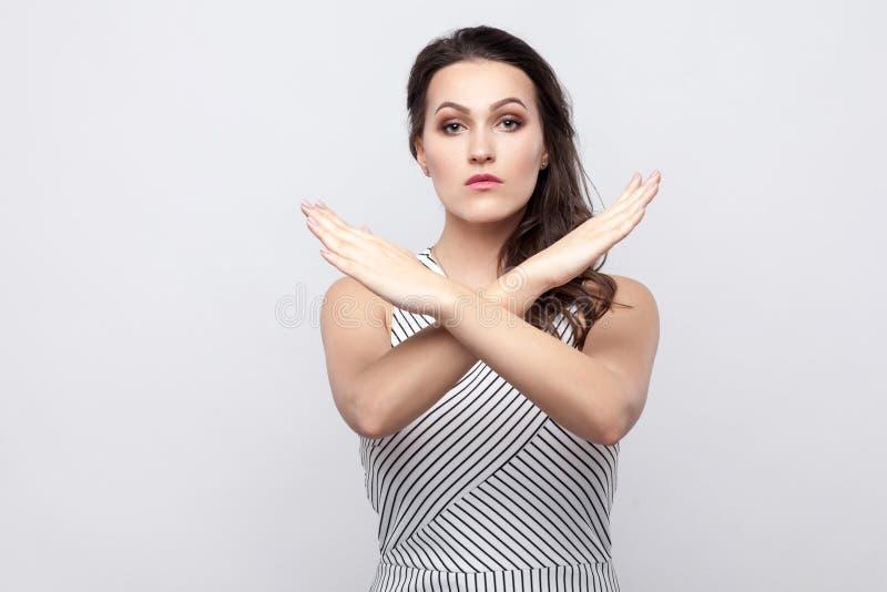 Er is geen manier Portret van ernstige mooie jonge donkerbruine vrouw met make-up en gestreepte kleding die zich met gekruiste ha stock foto