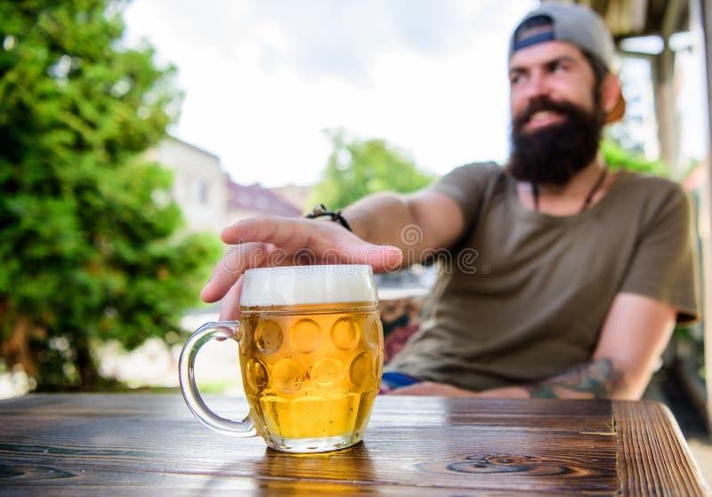 Er hat die schlechte Gewohnheit des Trinkens zu vielen Bieres Gekühlter Bierkrug auf Tabelle Trinkendes Bier des bärtigen Mannes  lizenzfreies stockfoto