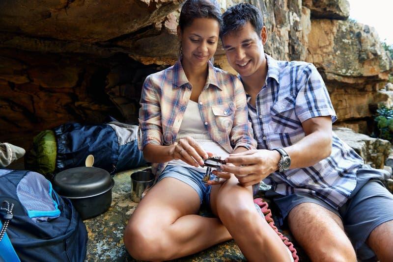 Er hilft ihr mit einem Teil des Gasbrennerofens lizenzfreie stockfotos