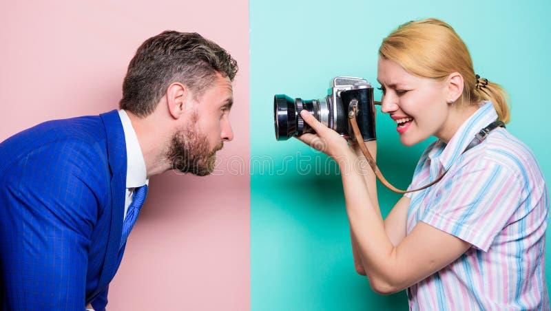 Er ist fotogen Hübsche Frau, die Berufskamera verwendet Geschäftsmann, der vor weiblichem Fotografen aufwirft stockfotos