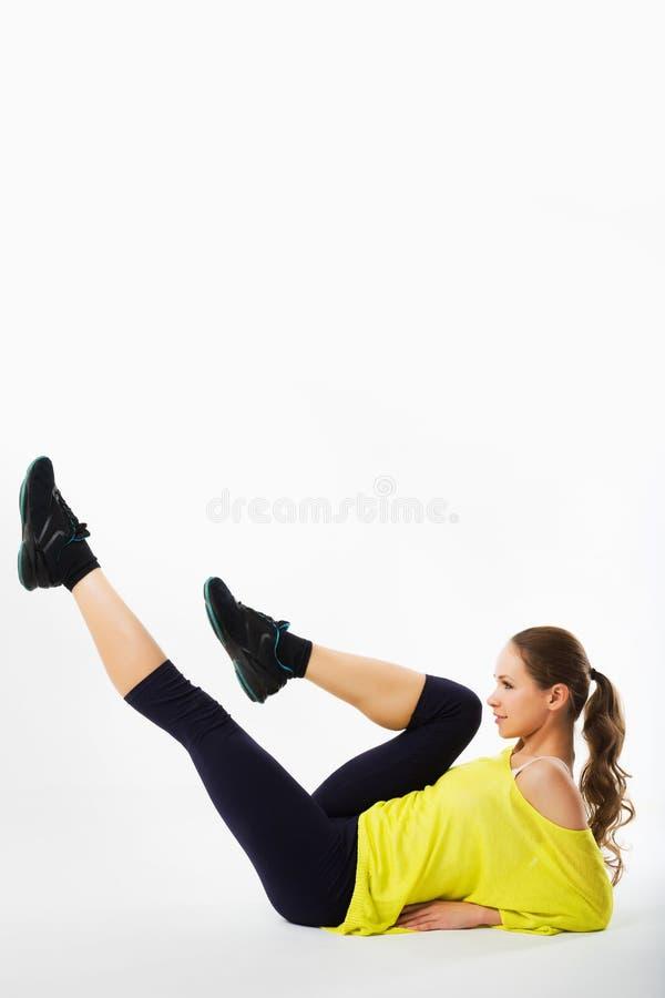 Er schöne sportliche Frau tut Übungen auf einem Boden Eignung stockfotos