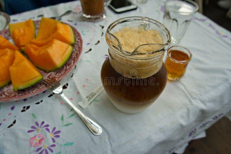 Er zijn de plakken van de Kantaloepmeloen en een glas bevroren koffie Latte is op de lijst royalty-vrije stock afbeelding