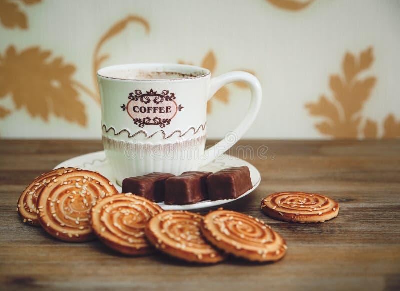 Er zijn Koekjes, Chocoladesuikergoed, Porseleinschotel en GLB met Coffe, Smakelijk Zoet Voedsel op de Houten Gestemde Achtergrond royalty-vrije stock foto's
