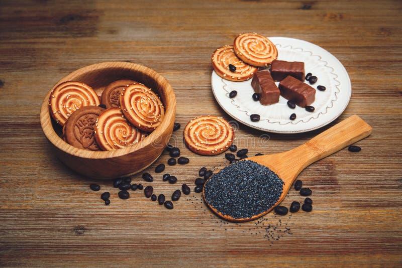 Er zijn Koekjes, Suikergoed, Chocoladeerwten, Papaver; Ceramische Plaat; Smakelijk Zoet Voedsel op de Houten Gestemde Achtergrond stock foto's