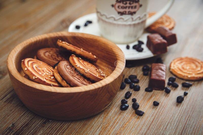 Er zijn Koekjes, Suikergoed, Chocoladeerwten, Papaver; Porseleinschotel en GLB met Coffe, Smakelijk Zoet Voedsel op de Houten Ges royalty-vrije stock afbeeldingen