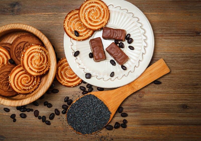 Er zijn Koekjes, Suikergoed, Chocoladeerwten, Papaver; Porseleinschotel, Smakelijk Zoet Voedsel op de Houten Achtergrond, Hoogste royalty-vrije stock afbeelding