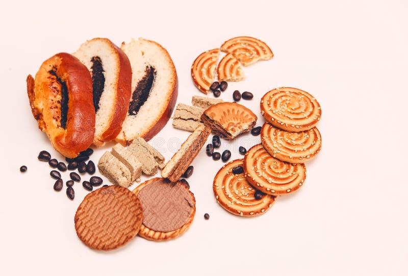 Er zijn Stukken van Broodje met papaverzaad, Koekjes, Halavah, Chocoladeerwten, Smakelijk Zoet Voedsel op de Witte Achtergrond, H royalty-vrije stock afbeelding