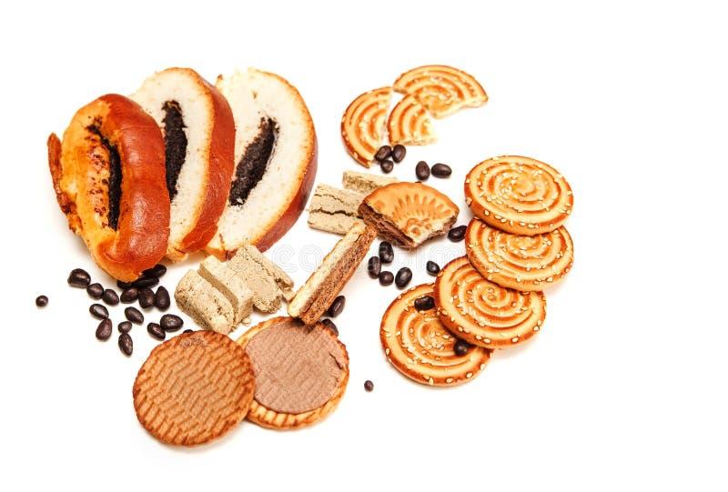 Er zijn Stukken van Broodje met papaverzaad, Koekjes, Halavah, Chocoladeerwten, Smakelijk Zoet Voedsel op de Witte Achtergrond, H stock afbeelding