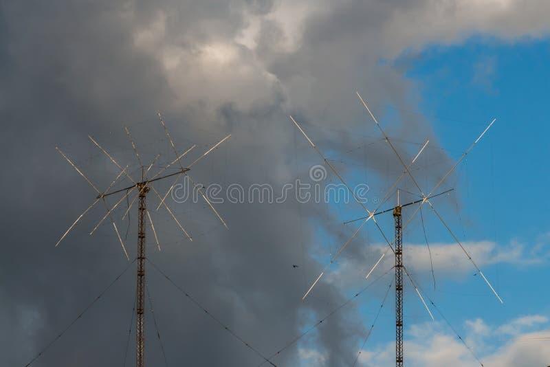 Er zijn twee metaal Amateur Radiohamantennes op de blauwe hemel met grijze en witte wolkenachtergrond stock foto