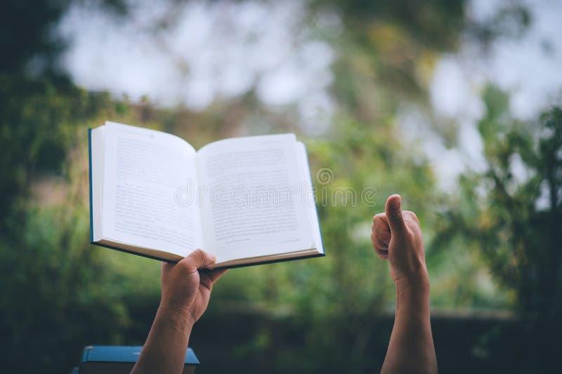 Er zijn zakenlieden die een boek van vreugde, de uitdrukking van een succesvolle zakenman houden En er is een exemplaarruimte stock fotografie