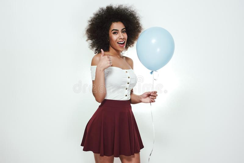 Era a melhor festa de anos! Retrato do polegar afro-americano alegre e feliz da exibição da mulher acima, guardando o azul fotos de stock