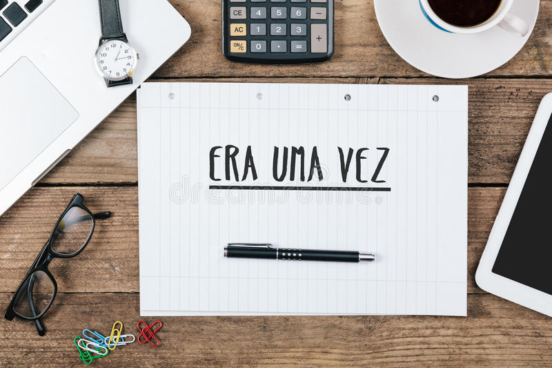 Era uma vez, Portuguese text for Once Upon a Time on note pad at. Era uma vez, Portuguese text for Once Upon a Time, on note pad at office desk with electronic stock photos