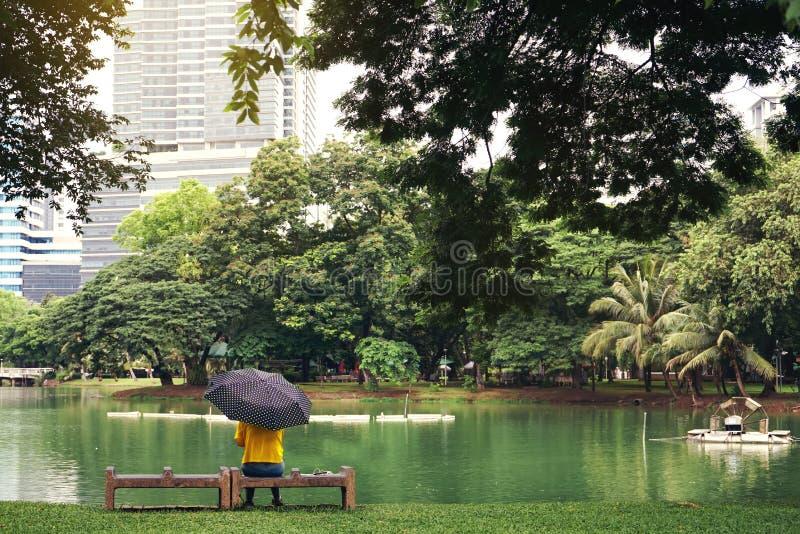 Erachter gezien van De jonge vrouw met parapluzitting dichtbij de vijver in Lumpini-park en kijkt vooruit Droevig en eenzaam royalty-vrije stock afbeelding