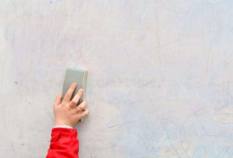 Erases della mano della scolara sulla lavagna immagine stock libera da diritti