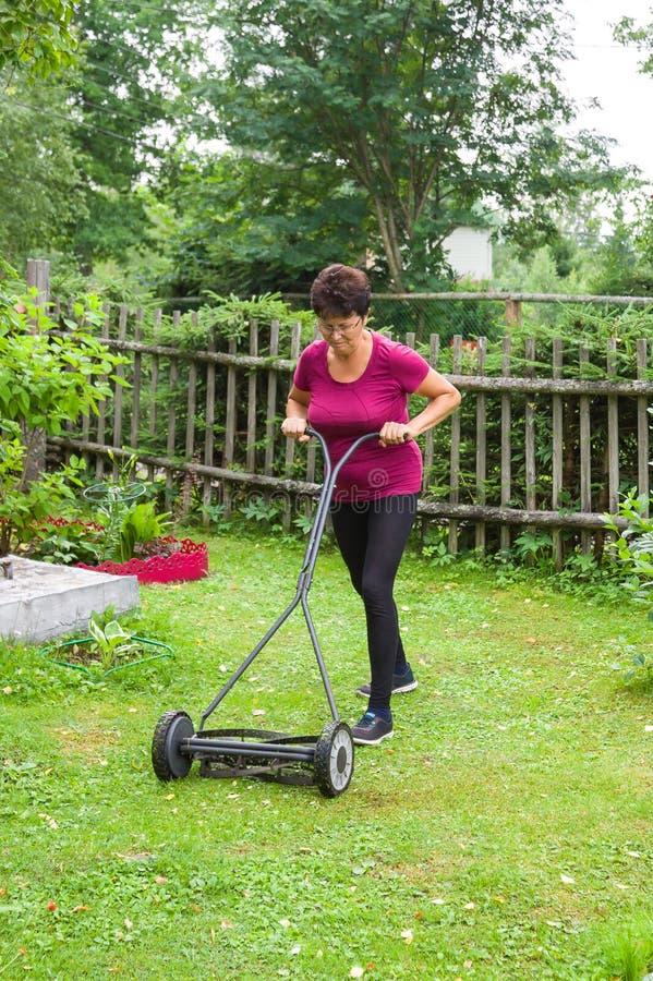 Erba di falciatura della donna senior con la falciatrice da giardino nel giardino immagini stock
