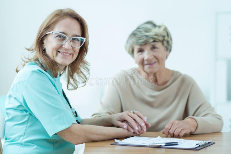 Erba medica femminile gentile con il paziente fotografie stock